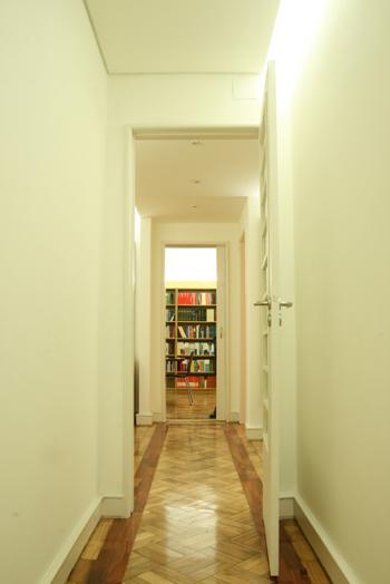 Vista do corredor dos gabinetes para a recepção e sala de reuniões ao fundo.