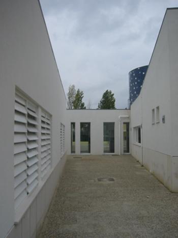 Vista exterior do espaço entre o corpo existente de salas de aula e o corpo dos serviços administrativos